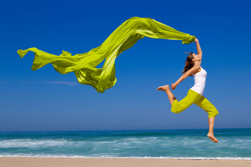 Woman running and jumping on sand shoreline of beach with green scarf.